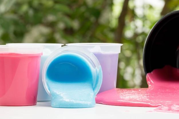 Butelki domowej roboty bawiące się szlamem, kolorowe zabawki nauki w pojemniku wyciek na stole, selektywne focus na szlamie.