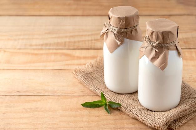 Butelki ekologicznego kefiru, jogurtu lub ajranu na drewnianym stole, wolna przestrzeń. fermentowane produkty mleczne