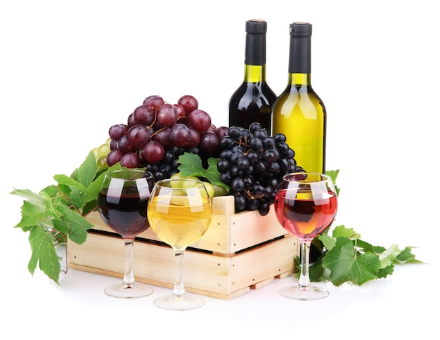 Butelki i kieliszki wina i asortyment winogron w drewnianej skrzyni, na białym tle