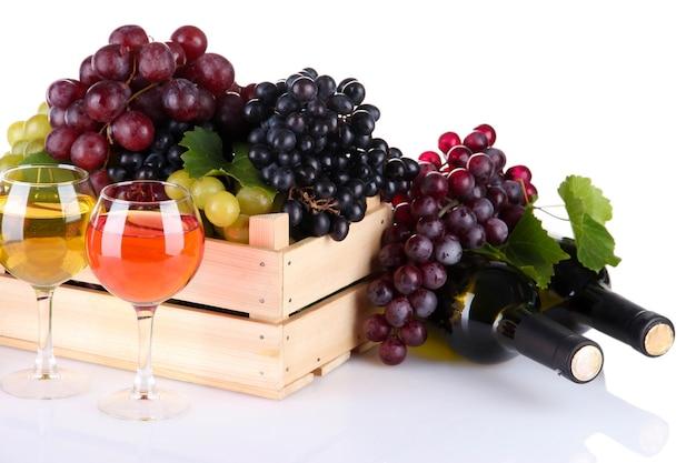 Butelki i kieliszki wina oraz asortyment winogron w drewnianej skrzyni, na białym tle