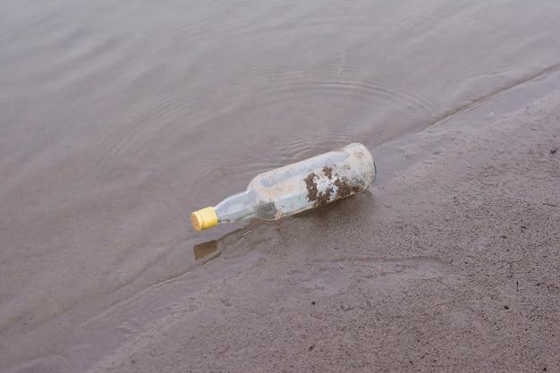 Butelki i śmieci na brzegu rzeki.