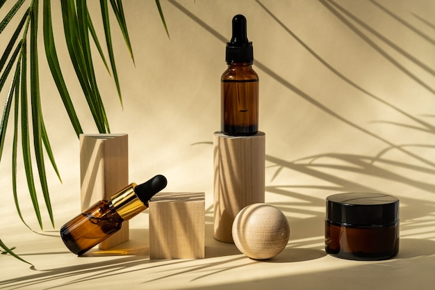 Butelki kosmetyczne bursztynowe z pipetą na drewnianych postumentach geometrycznych