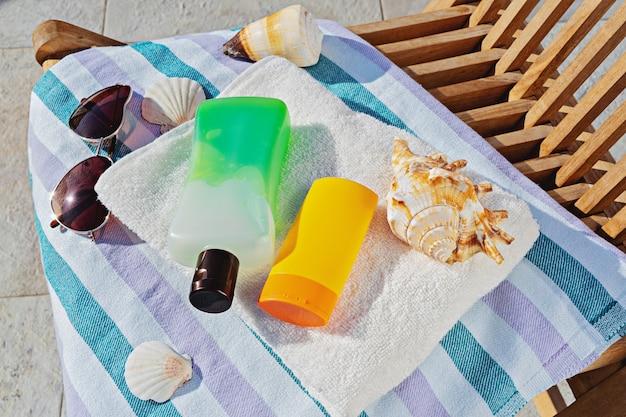 Butelki kosmetyczne i okulary przeciwsłoneczne w ręczniku na leżaku