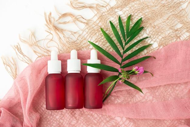 Butelki kosmetyczne, różowe słoiki z olejem,