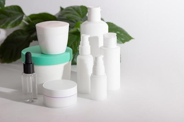 Butelki kosmetyczne stoją obok zielonych liści na białym tle. koncepcja kosmetyków organicznych