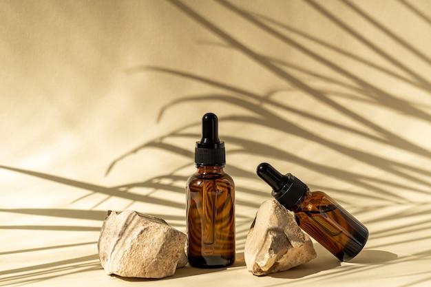 Butelki kosmetyczne z ciemnego szkła z zakraplaczem na beżowej powierzchni z kamieniami i tropikalnymi liśćmi