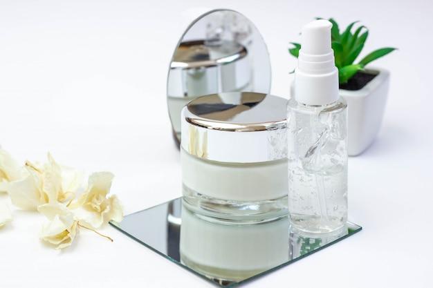 Butelki kosmetyczne z serum, żelem, kremem do twarzy na lustrze białe tło z kwiatkiem. kosmetyki do skóry, minimalizm