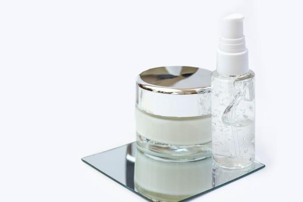 Butelki kosmetyczne z serum, żelem, kremem do twarzy na lustrze. kosmetyki do skóry, minimalizm