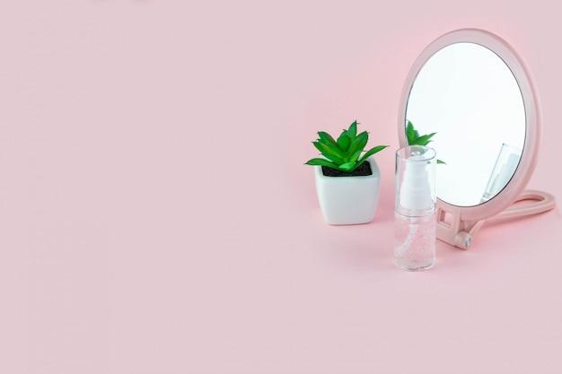 Butelki kosmetyczne z serum, żelem, kremem do twarzy na różowym tle z kwiatkiem i lustrem. kosmetyki do skóry, minimalizm