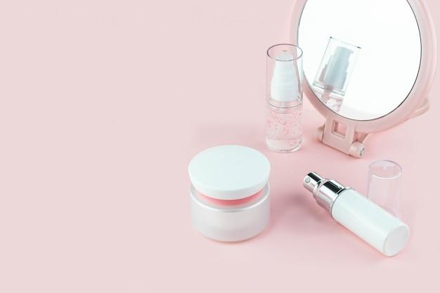 Butelki kosmetyczne z serum, żelem, kremem do twarzy na różowym tle z lustrem. kosmetyki do skóry, minimalizm