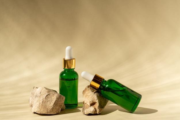 Butelki kosmetyczne z zielonego szkła z zakraplaczem na beżowej powierzchni z kamieniami i tropikalnymi liśćmi