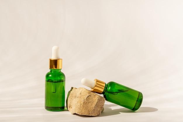 Butelki kosmetyczne z zielonego szkła z zakraplaczem na beżowej powierzchni z kamieniem