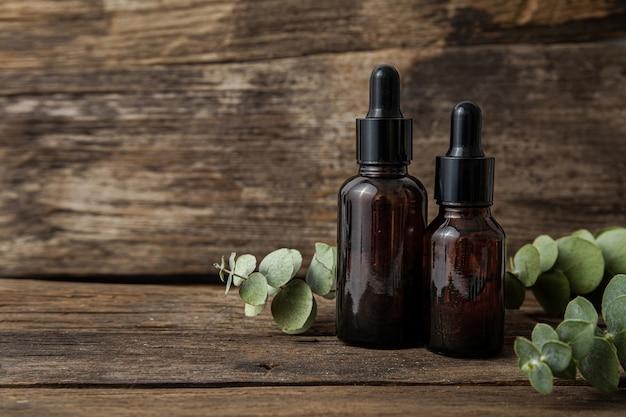 Butelki kosmetyczne ze szkła bursztynowego i świeże liście eukaliptusa na drewnie