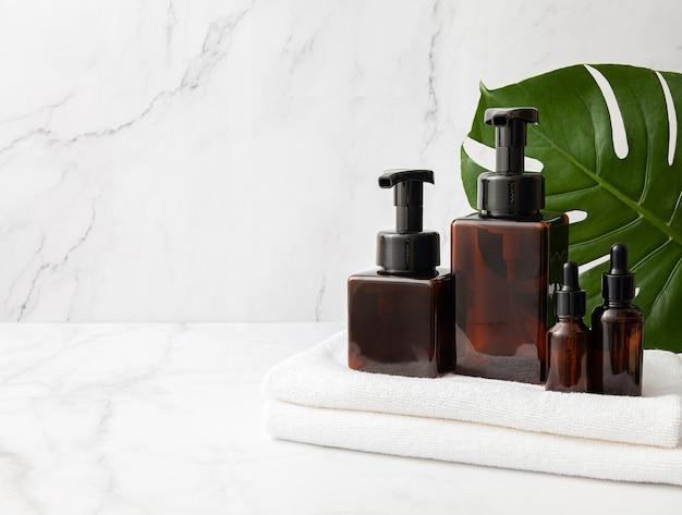 Butelki kosmetyczne ze szkła bursztynowego z ręcznikiem i zielonym liściem na tle marmuru. skopiuj miejsce