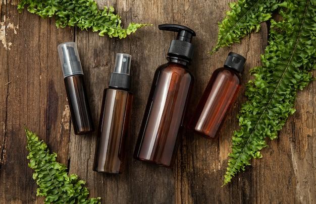 Butelki kosmetyczne ze szkła bursztynowego z zielonymi liśćmi na tle drewna. naturalna koncepcja. leżał na płasko, widok z góry.