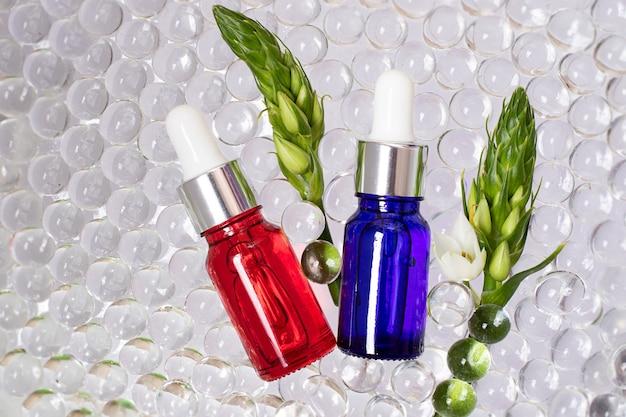 Butelki kosmetyków z czerwonego i niebieskiego szkła, widok z góry. przezroczyste kulki hydrożelowe wokół nich. zielone gałęzie z białym kwiatem, jak rama. koncepcja ekologiczna.