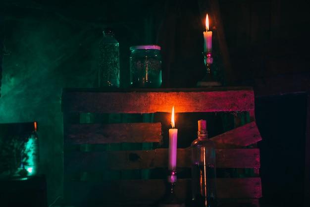 Butelki magicznych mikstur z trucizną w warsztacie wiedźmy alchemika