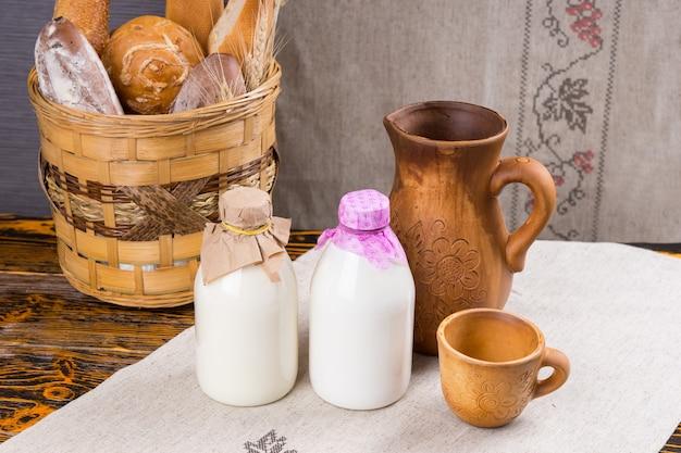 Butelki mleka obok drewnianego dzbanka i kubka na haftowanej serwetce z chlebem w starym okrągłym koszu