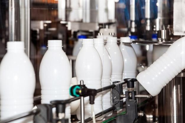 Butelki na mleko na przenośniku przemysłowym