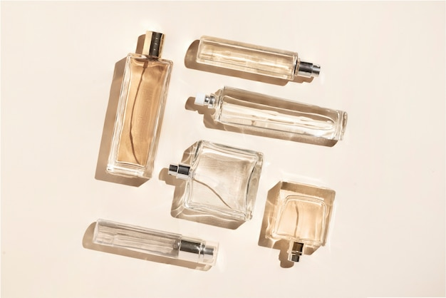 Butelki na perfumy w kolorze beżowym. flatlay martwa natura w stylu minimalizmu na kremowym tle, urodzie i modzie.