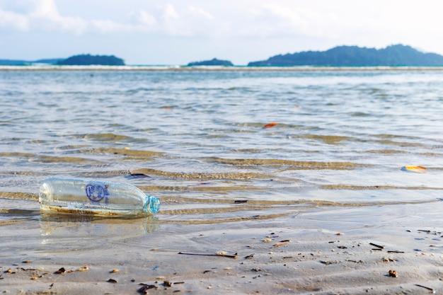 Butelki na ścieki, które pływają po plaży, problemy z zanieczyszczeniem środowiska przez ludzi.