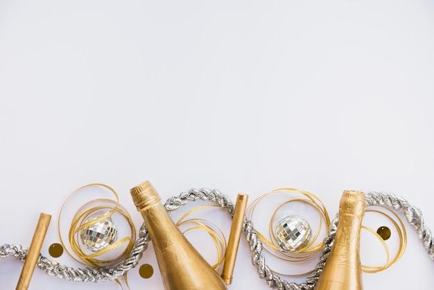 Butelki napoju w pobliżu świecidełek i wstążki