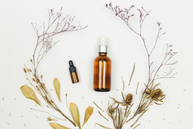 Butelki olejku kosmetycznego z suszonymi ziołami na białej powierzchni. wysokiej jakości zdjęcie