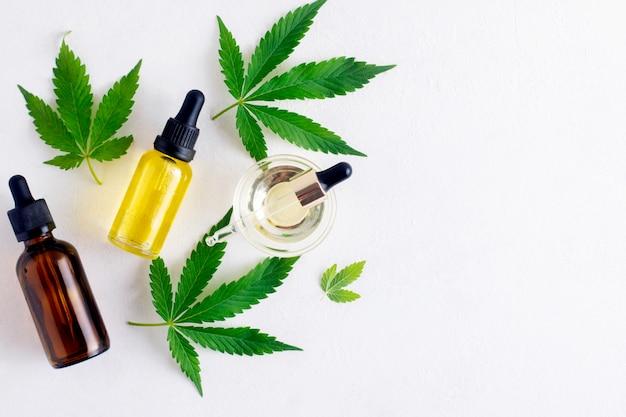 Butelki oleju cbd i liście konopi na białym tle z miejsca kopiowania. olej z olejem konopnym i liśćmi marihuany