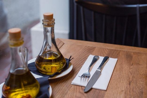 Butelki oleju i sztućce na drewnianym stole w kawiarni