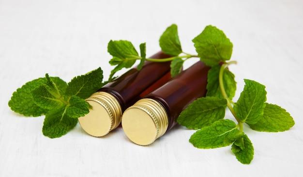 Butelki oleju miętowego i świeżej mięty