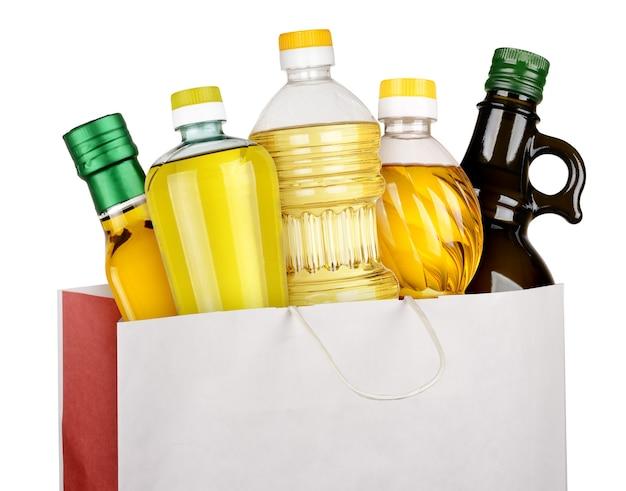 Butelki oleju w papierowej torbie na białym tle