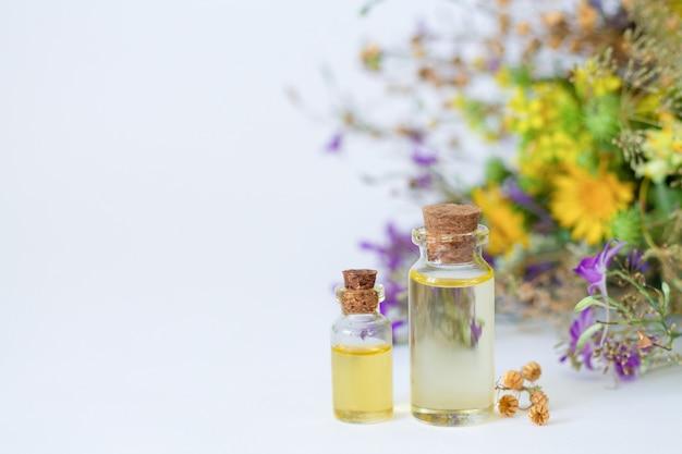 Butelki organicznego olejku eterycznego ze świeżymi i suszonymi ziołami leczniczymi i kwiatami na białym stole