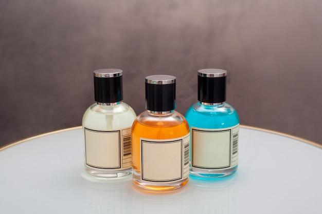 Butelki perfum w różnych kolorach leżą na stole, na tle sztruksu. pojęcie makiety perfum