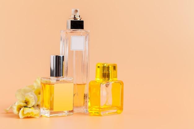 Butelki perfum z płatkami kwiatów na beżu