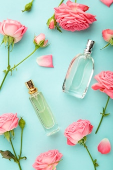 Butelki perfum z różowymi różami na miętowym tle.