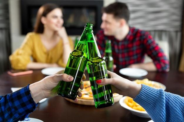 Butelki piwa. grupa przyjaciół korzystających z imprezy. ludzie piją piwo i śmieją się.