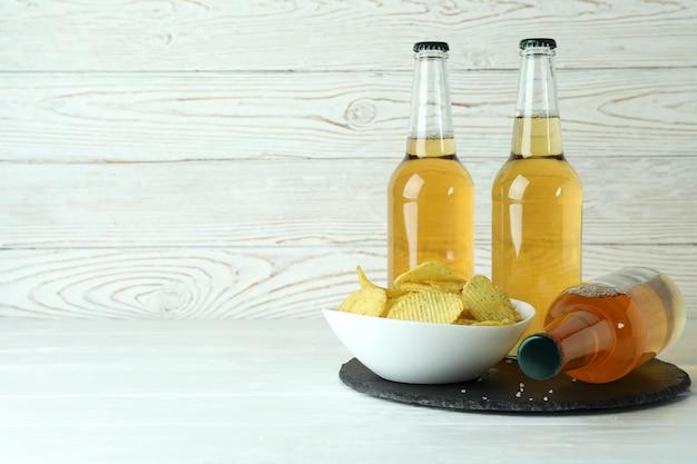 Butelki piwa i frytki na białym drewnianym
