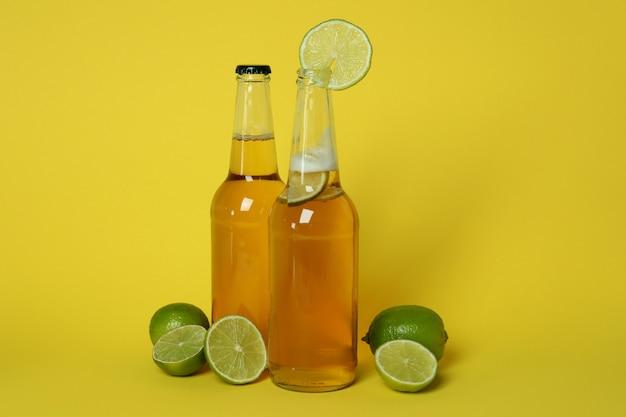 Butelki piwa i limonki na żółto