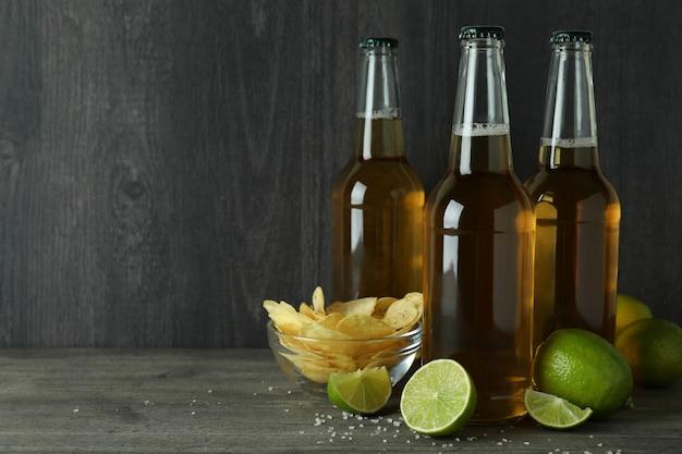Butelki piwa i przekąski na ciemnym drewnie