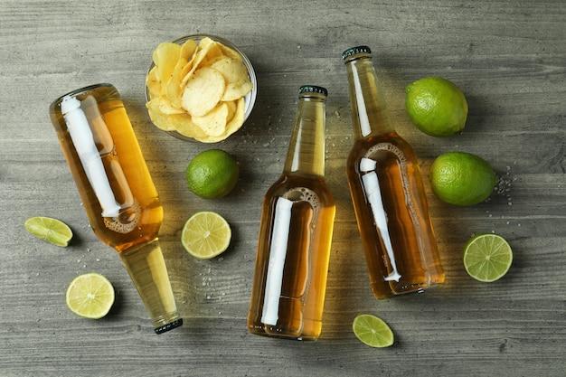 Butelki piwa i przekąski na szarym tle z teksturą