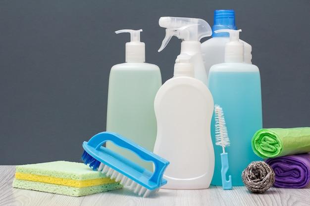 Butelki płynu do mycia naczyń, płyn do mycia szyb i płytek, płyn do kuchenek mikrofalowych i kuchenek, ścierki, szczotki, gąbka i worki na śmieci na szarym tle. koncepcja mycia i czyszczenia.