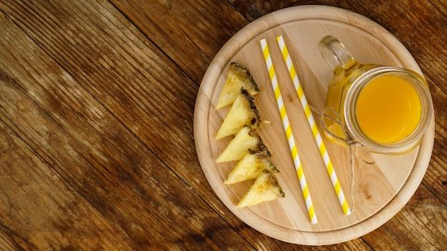 Butelki soku ananasowego na drewnianym stole. żółty napój i świeży ananas. przekąska w ośrodku. letnie zdjęcie. widok z góry