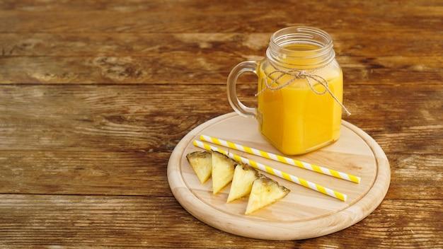 Butelki soku ananasowego na drewnianym stole. żółty napój i świeży ananas. przekąska w ośrodku na drewnianej tacy. letnie zdjęcie