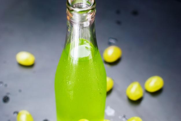 Butelki soku ze świeżych zielonych winogron ciemny stół