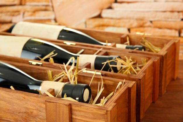 Butelki starego czerwonego wina w drewnianym pudełku, na kamieniu