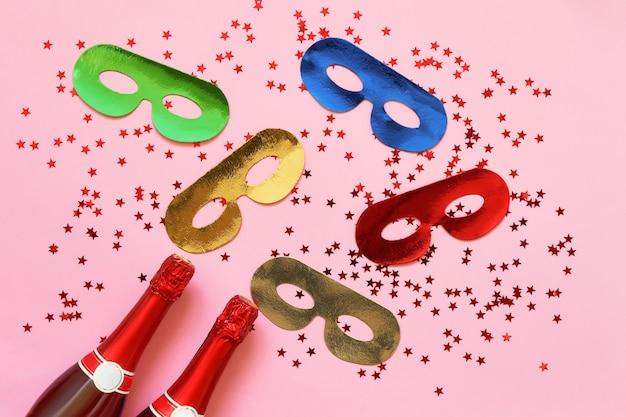 Butelki szampana, maski karnawałowe i gwiazdki konfetti na różowej ścianie