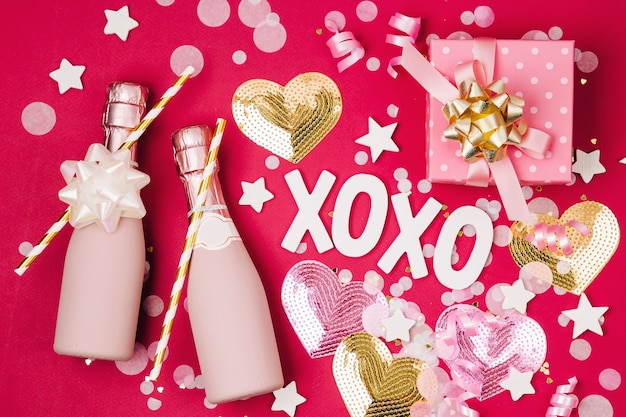 Butelki szampana z konfetti i blichtr na czerwonym tle. motyw koncepcyjny walentynki lub przyjęcie urodzinowe. płaski układanie, widok z góry