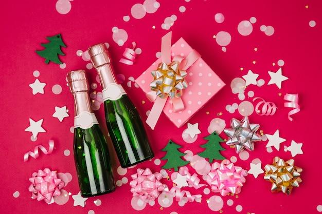 Butelki szampana z konfetti i blichtr na czerwonym tle. skład wakacje na obchody nowego roku lub bożego narodzenia. płaski układanie, widok z góry