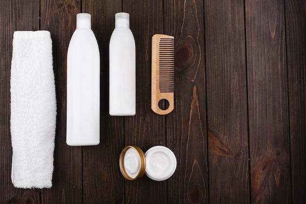 Butelki szamponu i odżywki leżą z ręcznikiem i grzebieniem na drewnianym stole