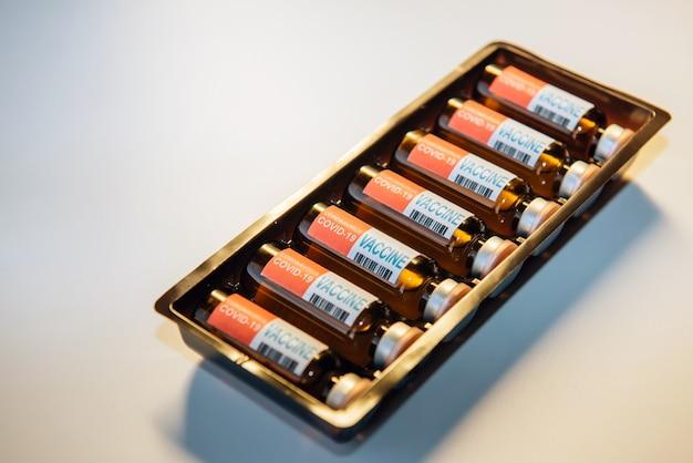 Butelki szczepionki do walki z pandemią koronawirusa. sars-cov-2 / covid-19. niektóre ampułki ze szczepionką w pudełku na białym stole, z bliska.